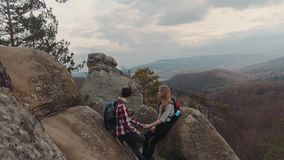 Teenagers in checkered shirts having a date on the rocky mountain top. Romantic time, holding their hands, chatting stock video footage