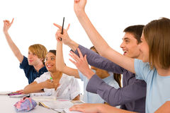 Teenagers in classroom with arms up Stock Photography