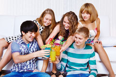 Teenagers clinking glasses Stock Images
