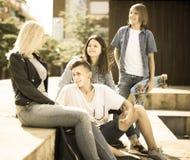 Teenagers communicate in schoolyard Stock Image