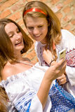 Teenagers Communication. Two young girls laughing looking in mobile phone Royalty Free Stock Photo