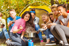 Teenagers cook soup in metallic pot during camping Royalty Free Stock Images