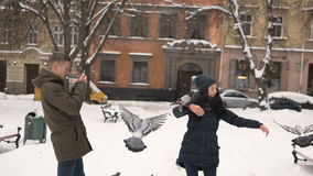 Teenagers Couple Seeding Doves. Couple of teenagers seeding city doves and having fun in winter time stock footage