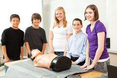 Teenagers with CPR Training Mannequin. Group of teenagers with a CPR training dummy, about to learn cardiopulmonary resuscitation Stock Image