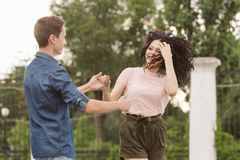 Teenagers on a date. A guy and a girl are dancing in a city park. Love and romance. Flirting. The first relationship. City life. Street fashion Stock Image