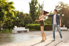 Teenagers on a date. The guy and the girl are whirling in the dance. The girl has curly hair. Love and romance. The first relationship. City life. Street royalty free stock photography