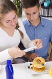 Teenagers decorating pancakes with berry Royalty Free Stock Photography