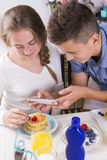 Teenagers decorating pancakes with berry Royalty Free Stock Photos