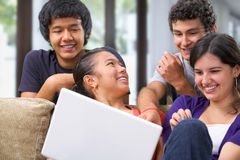 Teenagers discussing something on laptop Stock Photo