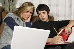 Teenagers doing homework with laptop Stock Images