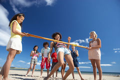 Teenagers doing limbo dance on beach Stock Photo