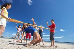 Teenagers doing limbo dance on beach. Having fun Stock Photo