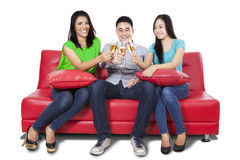 Teenagers drinking champagne on sofa Stock Images