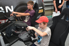 Teenagers drive simulators of racing game at the Nismo G-Drive S Stock Photo