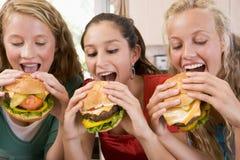 Teenagers Eating Burgers. Close Up Of Teenagers Eating Burgers Stock Photos