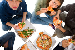 Teenagers eating pizza. Isolated on white background Royalty Free Stock Photography