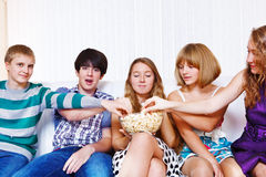 Teenagers eating popcorn. Teenagers group eating popcorn together Stock Photo