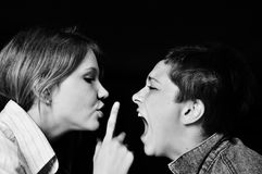 Teenagers emotions, problems. One girl becoming hysterical and anoter girl trying to make her calm down, asking her to be quieter. Photo in black and white Royalty Free Stock Photography