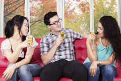 Teenagers enjoy champagne at home. Portrait of joyful teenagers drinking champagne on sofa with autumn background on the window Stock Photo