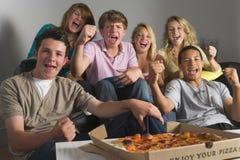 Teenagers Enjoying Drinks Together. Watching TV Stock Photography