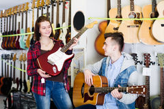 Teenagers examining both electric and acoustic guitars Stock Photos