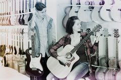 Teenagers examining both electric and acoustic guitars. Positive female and male teenagers examining both electric and acoustic guitars in guitar shop Royalty Free Stock Photography