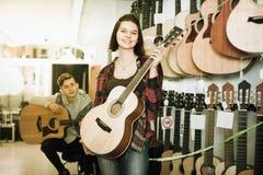 Teenagers examining guitars in shop Royalty Free Stock Photos