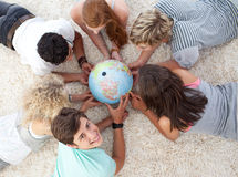 Teenagers examining a terrestrial globe. Group of teenagers lying on the floor examining a terrestrial globe royalty free stock photos