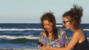 Teenagers excited when looking at a smart phone on the beach. Teenagers excited when looking at a smart phone and having fun on the beach stock video