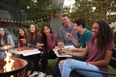 Teenagers at a fire pit eating take-away pizzas, close up royalty free stock photos
