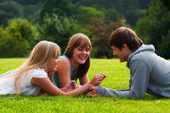 Teenagers flirting. Two girls and one guy flirting in a meadow Stock Images
