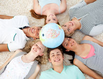 Teenagers on the floor with a globe in the center Royalty Free Stock Images