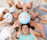 Teenagers on the floor with a globe in the center. Teenagers on the floor with a terrestrial globe in the center of their heads and with thumbs up Stock Image