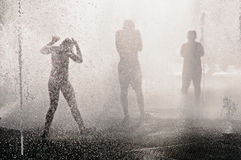 Teenagers in the fountain at the hot summer day Royalty Free Stock Photo