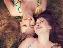 Teenagers friends lying on a grass laughing in a park Stock Images