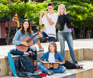 Teenagers friends playing musical instruments. Two positive girls and two glad boys teenagers friends with musical instruments together outdoors Royalty Free Stock Photos