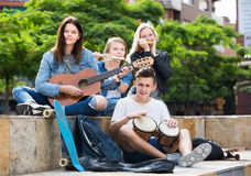 Teenagers friends playing musical instruments. Two positive girls and two happy boys teenagers friends with musical instruments together outdoors Stock Image