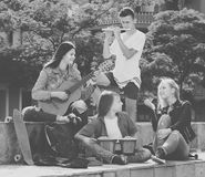 Teenagers friends playing musical instruments. Young teenagers friends with musical instruments together outdoors Stock Images
