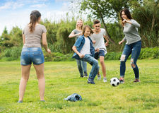 Teenagers friends running with ball. Three active girls and two boys teenagers friends running with ball on meadow outdoors Royalty Free Stock Image