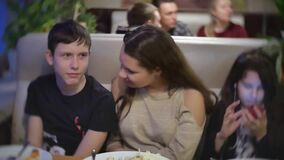 Teenagers friends are sitting in a cafe arguing jostling and talking swear. Adolescence problem social problem slow. Teenagers friends are sitting in cafe stock video footage