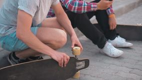 Teenagers friends with skateboards. Two friends skateboarders sitting on the street with skateboards and phone, street youth skateboarding lifestyle concept stock footage