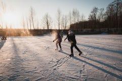 Teenagers frolic on the ice, winter fun girl skating royalty free stock photo