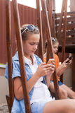Teenagers with gadgets. Sitting on the swings Stock Photos