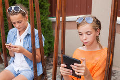 Teenagers with gadgets. Sitting on the swings Royalty Free Stock Photo