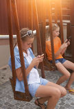 Teenagers with gadgets. Sitting on the swings Royalty Free Stock Image
