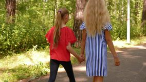 Teenagers girlfriend holding hands walking in summer park back view. Two girls walking on park pathway at summer day. Frienship and relationships stock video footage
