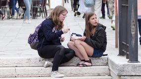 Teenagers girls eating junk food on street sitting on the steps. Burano, Italy 19 May 2018: teenagers girls eating junk food on street sitting on the steps in stock footage