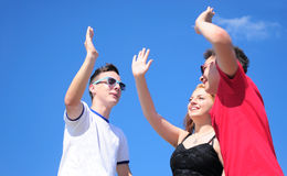 Teenagers giving five. Three happy friends. Teenage boys and girl giving a five, outdoor against summer blue sky Royalty Free Stock Image