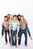 Teenagers giving their friends piggyback rides Royalty Free Stock Photo