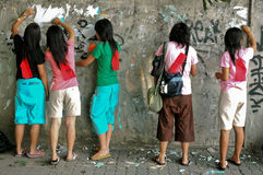 Teenagers group clean graffiti on old wall Royalty Free Stock Photos